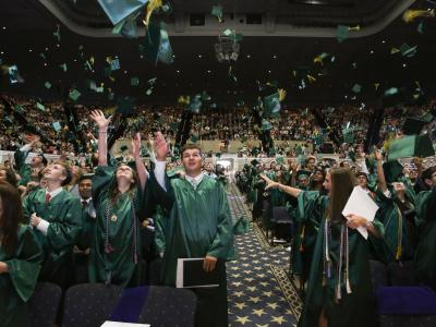 picture of graduates throwing caps in the air