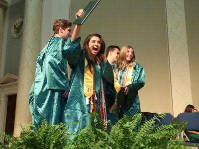 picture of class officers on stage in graduation robes at graduation ceremony